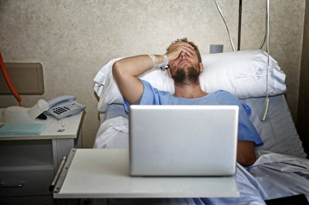 work injury: young man in hospital room lying in bed sick and injured using internet in computer laptop feeling sad and depressed researching info on his own disease injury or sickness Stock Photo