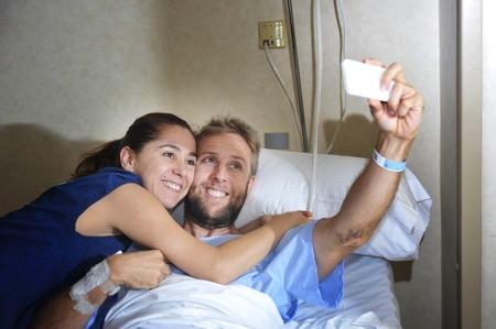 marido y mujer: joven pareja feliz en el amor tomar selfie foto a la habitaci�n del hospital con el hombre enfermo acostado en la cama en la cl�nica de la celebraci�n de tel�fono m�vil de suicidarse junto con su esposa o novia en concepto de pensamiento positivo Foto de archivo