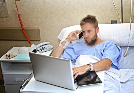 lesionado: joven hombre de negocios adicto al trabajo en el cuarto de hospital acostado en la cama de enfermedad o accidentes de trabajo con el teléfono móvil y ordenador portátil en el cuidado de la salud y el concepto de la obsesión de trabajo Foto de archivo