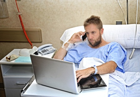 man in hospital bed: young workaholic business man in hospital room lying in bed sick and injured working with mobile phone and computer laptop in health care and work obsession concept Stock Photo