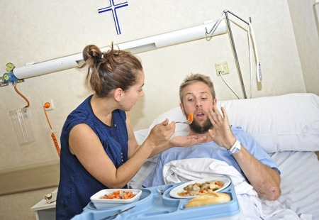 sick person: young wife trying to feed his husband lying in bed at hospital room ill after suffering accident and him looking unhappy with the diet food at the clinic center rejecting the meal