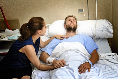 young sick man lying in bed at hospital room after suffering accident having his worried and caring wife or girlfriend together holding his hand giving him love and support Archivio Fotografico