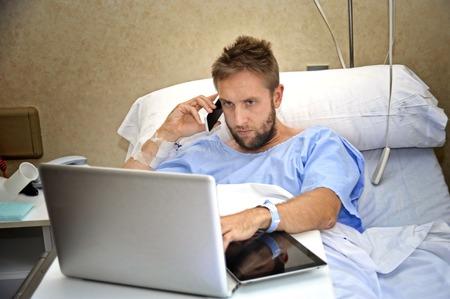 Jonge workaholic zakenman in het ziekenhuis kamer liggen in bed zieke en gewonde werken met mobiele telefoon en laptop in de gezondheidszorg en werk obsessie begrip Stockfoto - 42897231