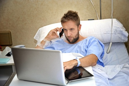 workaholic: young workaholic business man in hospital room lying in bed sick and injured working with mobile phone and computer laptop in health care and work obsession concept Stock Photo