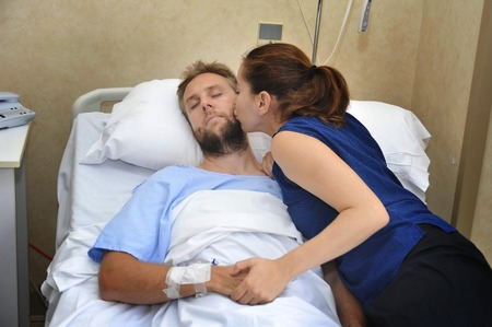 man in hospital bed: young sick man lying in bed at hospital room after suffering accident having his worried and caring wife or girlfriend together holding his hand kissing him giving love and support Stock Photo