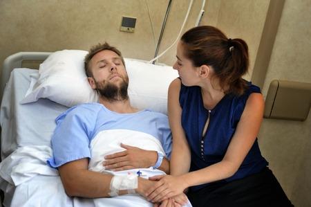 Jonge zieke man liggend in bed in het ziekenhuis kamer na het lijden van een ongeval met zijn bezorgd en zorgzame vrouw of vriendin samen met zijn hand die hem liefde en steun Stockfoto - 42897236