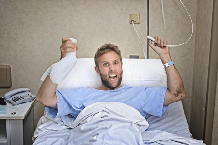 medical attention: young angry patient man at hospital room lying in bed pressing nurse call button holding potty feeling nervous and upset in pee help emergency health care and medical attention concept