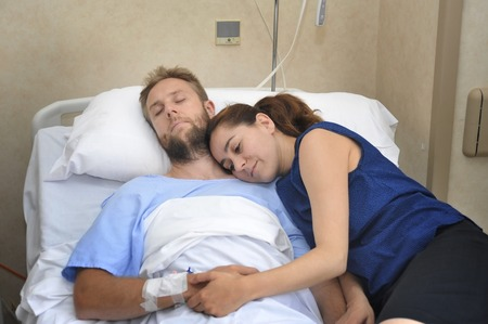 accident patient: young sick man lying in bed at hospital room after suffering accident having his worried and caring wife or girlfriend together holding his hand giving him love and support Stock Photo