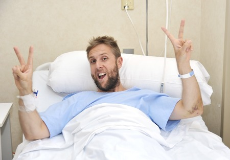 healthy looking: young American man lying in bed at hospital room sick or ill but making victory sign with fingers smiling happy and positive fighting against disease with energy