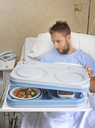 lunch tray: young patient man in hospital room after suffering accident opening meal tray ready to have a healthy diet clinic lunch in medical and health care centers food quality concept