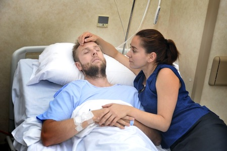 sad couple: young sick man lying in bed at hospital room after suffering accident having his worried and caring wife or girlfriend together holding his hand giving him love and support Stock Photo