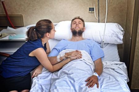 若い病人彼心配した事故と思いやりのある妻やガール フレンドが一緒に彼の愛とサポートを与える彼の手を握ってに苦しんでいる後病室でベッドに