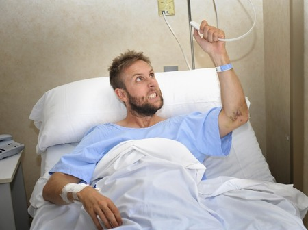 medical attention: young angry patient man at hospital room lying in bed pressing nurse call button feeling nervous and upset in some kind of emergency health care and medical attention concept