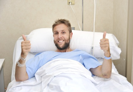 healthy looking: young American man lying in bed at hospital room sick or ill but giving thumbs up smiling happy and positive fighting against disease with energy