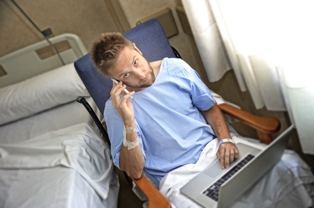 sick: young workaholic business man in hospital room sick and injured after accident working with mobile phone and computer laptop in health care and work obsession concept