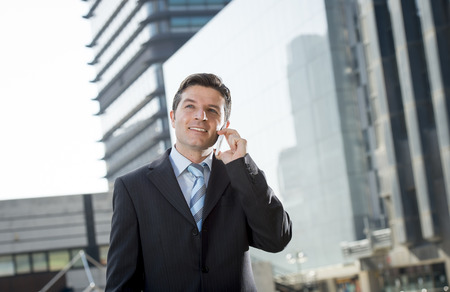 attractive people: young attractive businessman in suit and necktie talking on mobile smart phone smiling happy and confident standing outdoors in exterior office buildings on business district in success concept