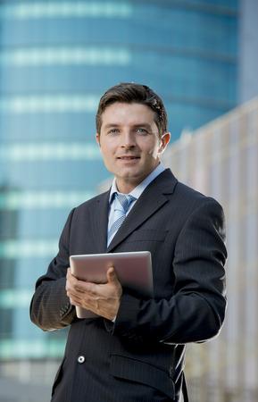 empleados trabajando: joven atractivo hombre de negocios en traje y corbata celebración de la tableta digital pie al aire libre de trabajo en edificios de oficinas exteriores en el distrito de negocios que parece feliz y relajado en el éxito concepto de trabajo
