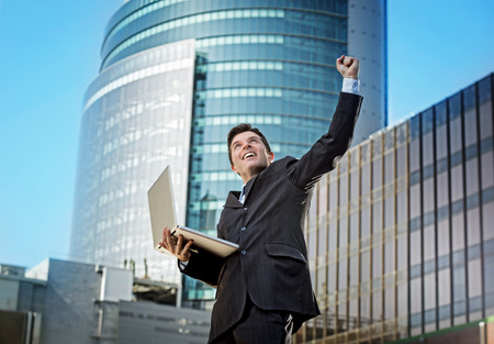 happiness or success: young attractive and successful businessman in suit and tie with computer laptop happy and excited doing victory sign after reaching business goal outdoors at urban city financial district