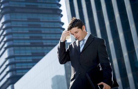 obreros: joven hombre de negocios agotado y preocupado pie al aire libre en la calle en frente de los edificios de negocios en el distrito financiero parece triste en el estr�s laboral y dolor de cabeza celebraci�n caf� para llevar