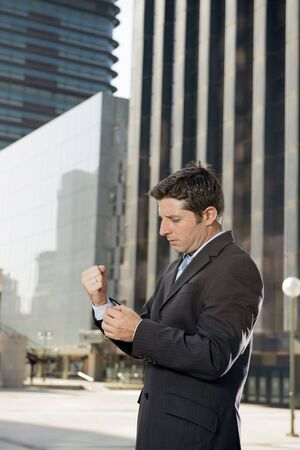 cuff: young attractive executive businessman adjusting shirt cuff link standing outdoors at exterior office building in financial district ready for success in the city Stock Photo
