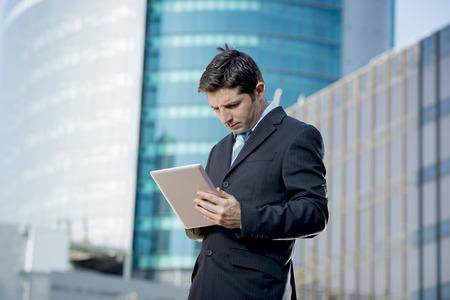 empleados trabajando: joven atractivo hombre de negocios en traje y corbata sosteniendo digitales de pie tablilla al aire libre de trabajo en edificios de oficinas exteriores en el distrito de negocios que parece preocupado y pensativo en concepto de estrés laboral