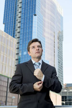 cuff link: young attractive executive businessman adjusting shirt cuff link standing outdoors at exterior office building in financial district ready for success in the city Stock Photo