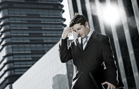 financial: young exhausted businessman standing outdoors on street in front of business buildings at financial district suffering headache and work stress holding take away coffee