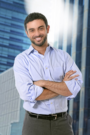 human arm: young attractive business man posing happy in corporate portrait outdoors on financial district background smiling with folded arms wearing casual businessman clothes in success concept