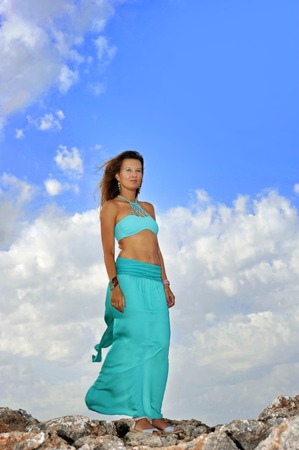 contemplative: young attractive woman with cyan dress looking thoughtful and contemplative at horizon standing on rocks under a summer blue sky in beauty and relax concept