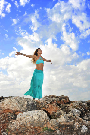 spiritual: young attractive woman with cyan dress and opened arms in Zen yoga pose at rock mountain looking at horizon under blue sky with clouds in relax and spiritual serenity and freedom concept