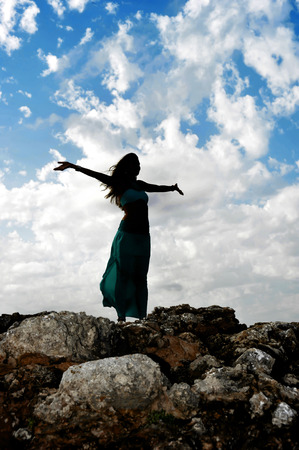 Silhouette of young attractive woman with dress and opened arms in Zen yoga pose at rock mountain looking at horizon under blue sky with clouds in relax and spiritual serenity and freedom concept