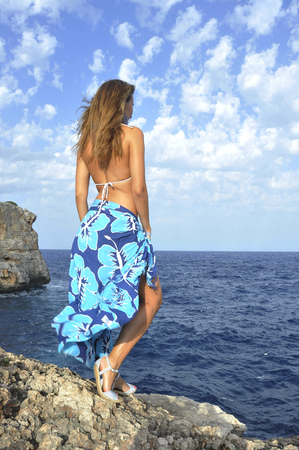 beach wrap: young attractive woman looking at ocean horizon standing on rock cliff by sea shore in sarong beach wrap and bikini under summer blue sky in relax and vacation concept
