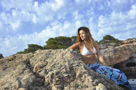 beach wrap: young attractive woman looking at ocean horizon leaning on rock cliff by sea shore in sarong beach wrap and bikini under summer blue sky in relax and vacation concept
