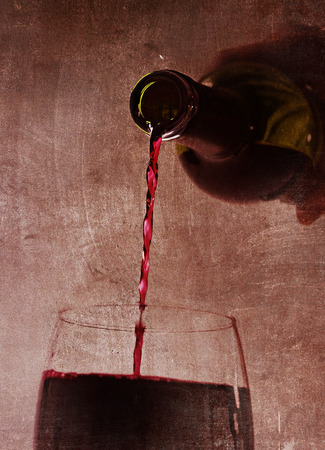 hand holding bottle: Close up view of Man hand holding Bottle pouring Spanish red wine filling Glass on a dark grunge arty background in luxury gourmet and expensive winery concept