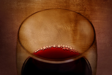 arty: Close up view of  Spanish red wine Glass with bubbles on a dark grunge arty background in luxury gourmet and expensive winery concept