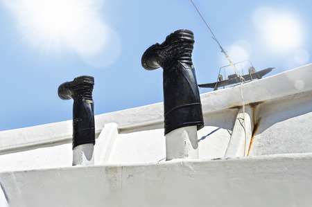work boat: boots of a fisherman put to dry under Summer sun on the deck of the boat in sea fishing work lifestyle and sailor concept Stock Photo