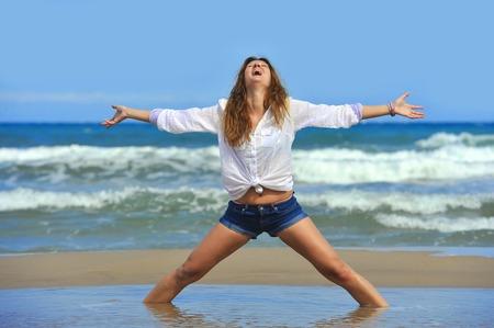beine spreizen: junge attraktive Frau in Shorts und T-Shirt am Strand mit Meer auf dem Rücken mit ausgebreiteten Armen und Beinen und Kopf in den Himmel in sich entspannen und Freiheit Konzept