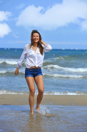 wet jeans: young beautiful girl walking on water at sea shore wearing shorts and shirt smiling happy in beach holiday fun and relax concept