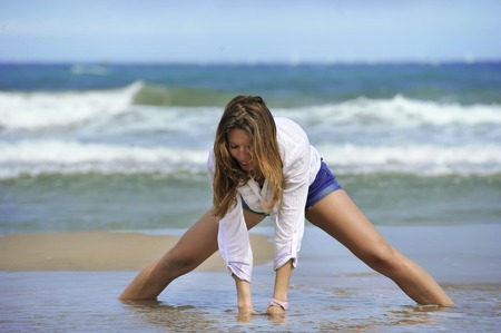 wet jeans: young attractive woman in shorts and shirt playing with sand on the beach with sea on her back with spread legs in relax and freedom concept
