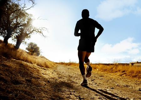 cross legs: Silhouette of young sport man running on countryside in cross country workout at summer sunset with  harsh sunlight effect in healthy lifestyle concept