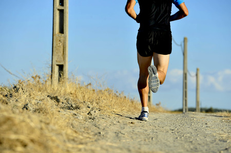 cross legs: back view of young sport man legs and feet running on countryside track with power line poles training in summer harsh light in cross country runner concept and healthy fitness lifestyle