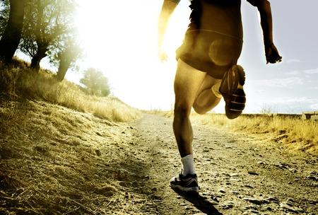 pies: cerrar las piernas y los pies de la silueta de extrema hombre corriendo a campo traviesa y capacitaci�n sobre pista de jogging rural al atardecer con la luz solar dura y reflejo en la lente en el deporte rural y el concepto de estilo de vida saludable Foto de archivo