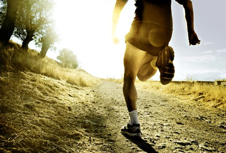 man rear view: close up silhouette legs and feet of extreme cross country man running and training on rural track jogging at sunset with harsh sunlight and lens flare in countryside sport and healthy lifestyle concept