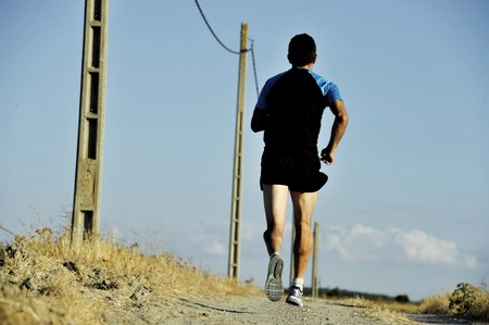 harsh: back view of young sport man running on countryside track with power line poles training in summer harsh light in cross country runner concept and healthy fitness lifestyle Stock Photo