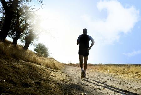 健康的なライフ スタイルのコンセプトで過酷な日光の効果と夏の夕暮れ時国トレーニング クロスの田舎で走っている若いスポーツ人のシルエット 写真素材