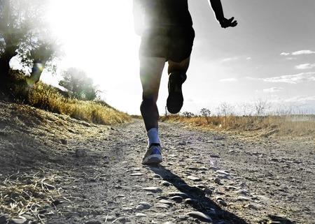 pista de atletismo: cerrar las piernas y los pies de la silueta de extrema hombre corriendo a campo traviesa y capacitación sobre pista de jogging rural al atardecer con la luz solar dura y reflejo en la lente en el deporte rural y el concepto de estilo de vida saludable Foto de archivo