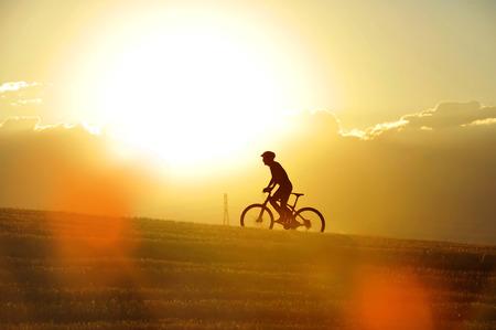 silueta ciclista: silueta de perfil de hombre de deporte en bicicleta cuesta arriba cruz ciclismo de montaña del país en el campo de la puesta de sol con la cruda luz del sol y de alto contraste en la sorprendente belleza del paisaje rural, con reflejo en la lente de color naranja