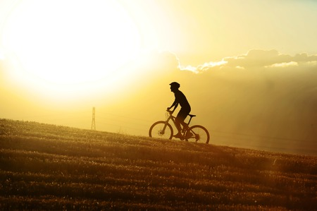 profile silhouette of sport man cycling uphill riding cross country mountain bike on sunset field with harsh sun light and high contrast in amazing beautiful rural landscape with orange lensflare Stock Photo