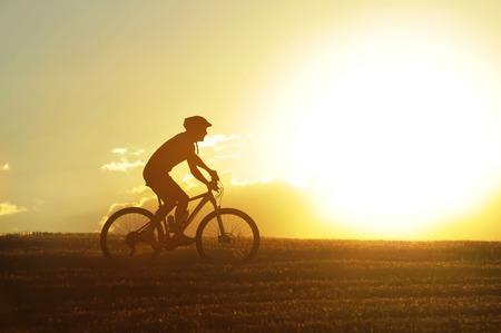 silueta ciclista: silueta de perfil de hombre de deporte en bicicleta cuesta arriba cruz ciclismo de montaña del país en el campo de la puesta de sol con la cruda luz del sol y de alto contraste en la sorprendente belleza del paisaje rural, con reflejo en la lente