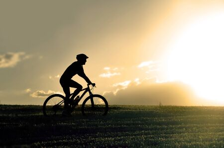 harsh light: profile silhouette of sport man riding cross country mountain bike on sunset field with harsh sun light and high contrast in amazing beautiful rural landscape Stock Photo